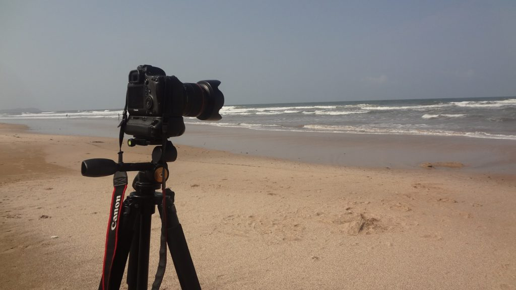 A camera mounted on a tripod facing the ocean on a beach.