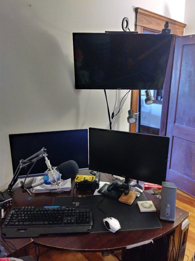 My streaming setup. Two monitors and an overhead TV, A Keyboard, XLR mic and interface(partially visible), and mouse. In the background, my light stand. Many of these items or equivilant are on sale for Amazon Prime day.