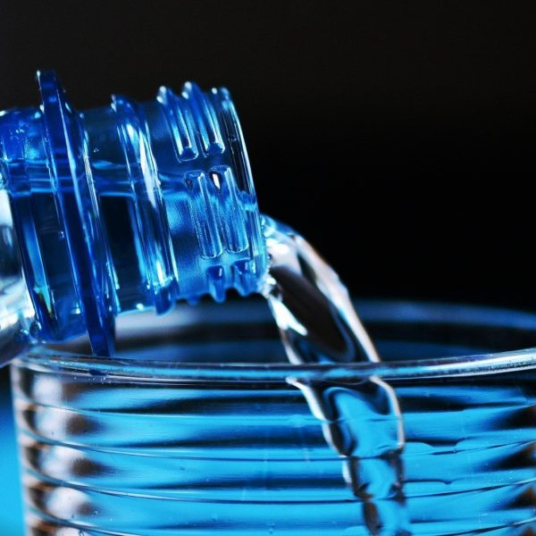 A water bottle being emptied into a glass with a blue-black background out of focus