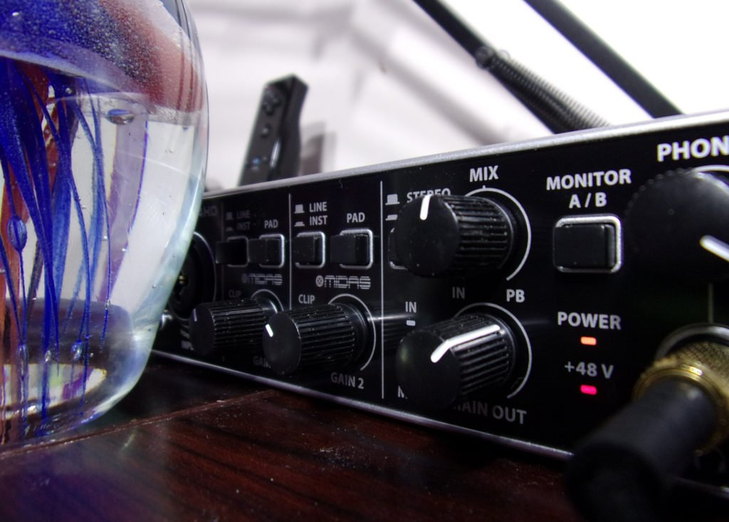 Picture of the Behringer UMC204HD. On the left is a partially hidden glass egg with a jellyfish inside it, for composition. In the background, a wii controller can be seen blurred out. On the right, The blurred outv image of the microphone boom arm can be seen extending up and out of frame shaped like this. \\