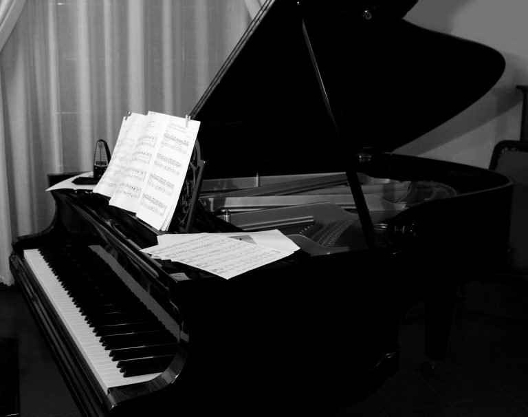 Music on Stream. Represented by a Black and white photo of a Grand Piano.