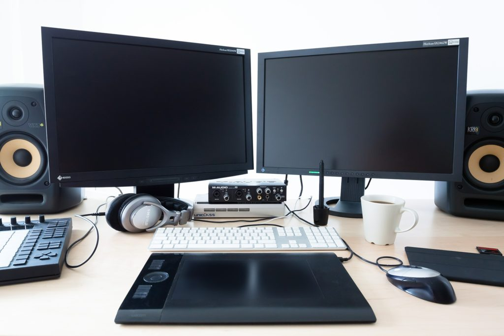 The background color is white. Near the top of the image are two monitors, angled in a wide V shape. To either side of them, are two high end studio monitors (expensive studio equipment). At the bottom, is a Black drawing pad. Above that is a silver-white keyboard. To the right, a silver and black mouse. Located to the right of the mouse is a black mousepad. Above that mousepad at the edge of the image is an sd card? Its hard to tell. To the left of that is a white mug of slightly steaming coffee. Just above the keyboard is a charger for a wireless pen for the drawing pad. Further to the left, located underneath and behind the set of monitors are two boxes. The first box is a...DVD player, I think. I'm not familiar. It has the Uniclass logo. The Second box is an Audio interface by M-Audio. It is at least a two port xlr input.